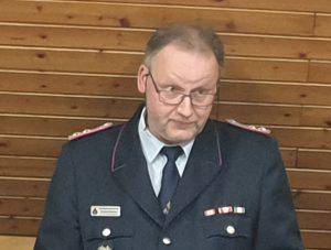 Ortsbrandmeister eröffnet in leicht gebückter Haltung die Versammlung und hält seinen Jahresbericht