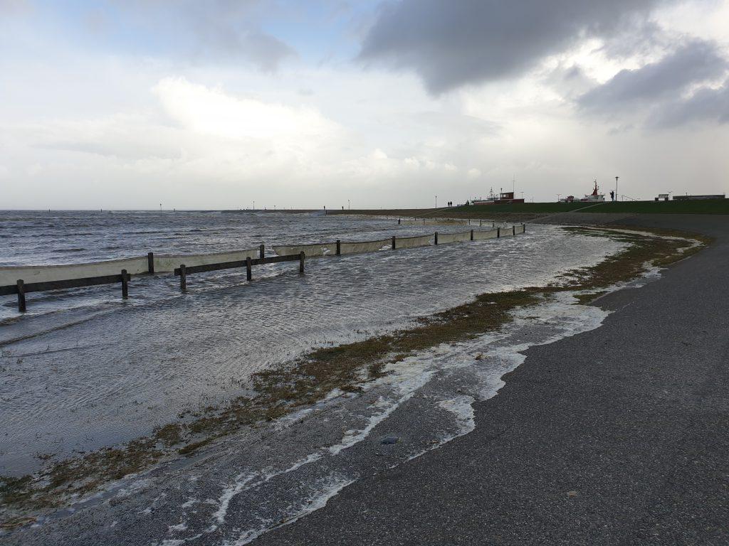 Der Strand in Neuharlingersiel ist komplett überspült; das Wasser reicht bis an den Deichfuß