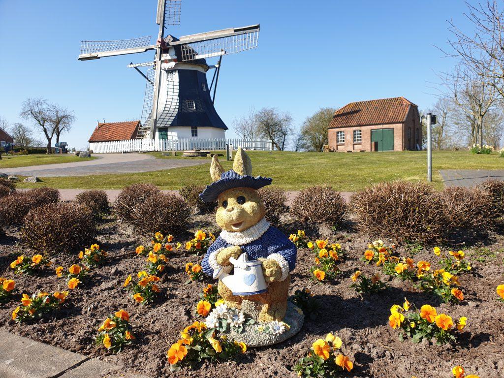 Es grüßt der Osterhase vor der Museumswiese mit Mühle und Schmiede