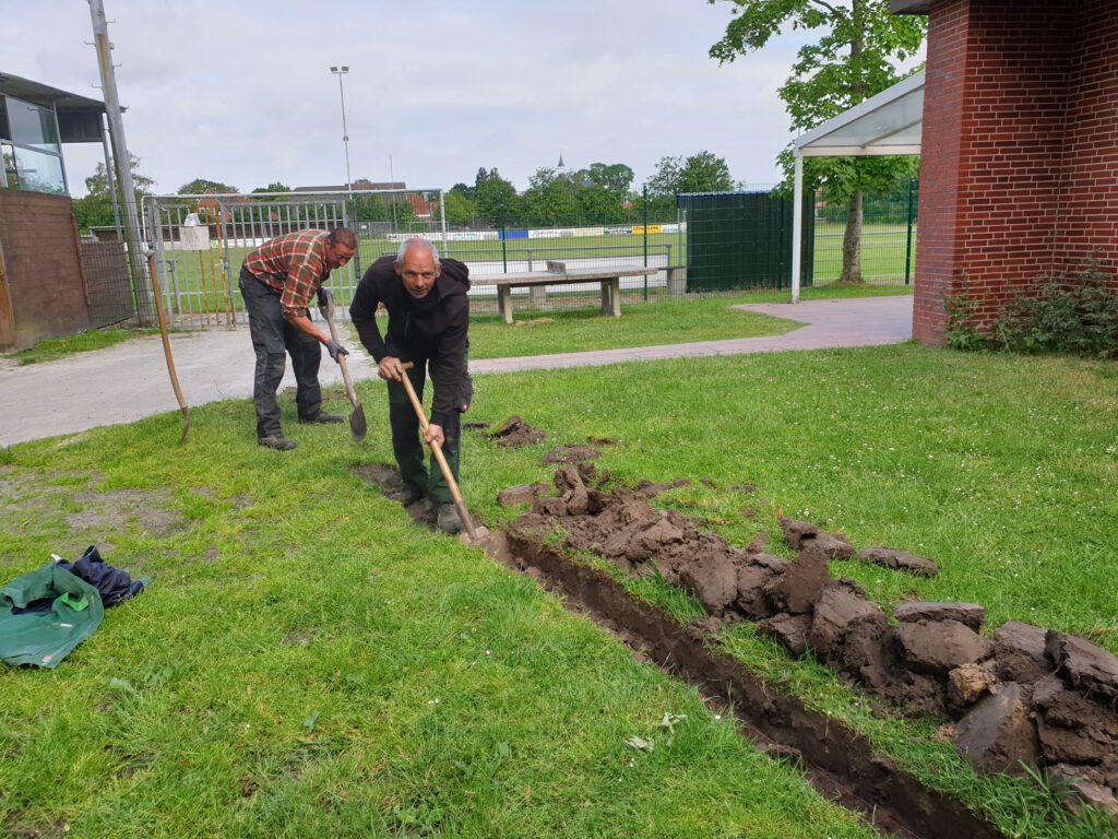 Johann Decker und Heiko Hohaus graben den Kabelkanal vom Schulgebäude bis zum Flutlichtmast