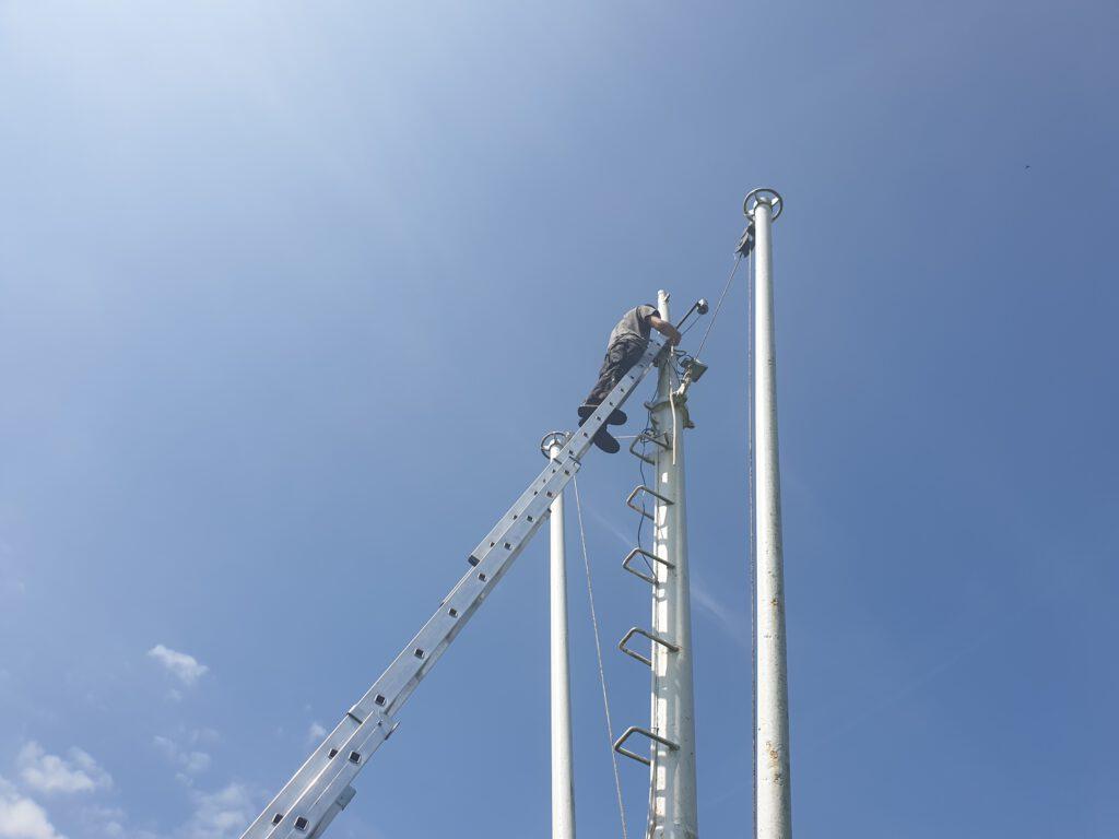 Hoch oben am Schiffsmast auf dem Dorfplatz montiert Bernhard Wagner die Geräte