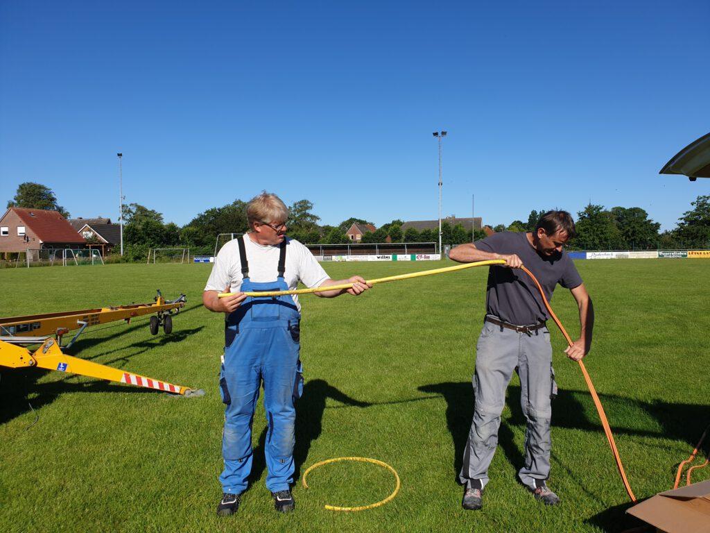 Holger Klattenberg und Bernhard Wagner führen das Glasfaser in eine Schutzhülle