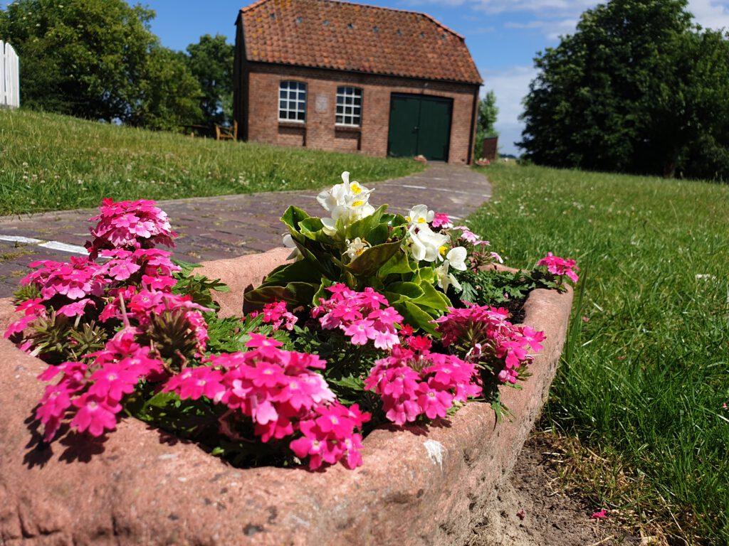Vorbei an Blumenkübel zur historischen Schmiede