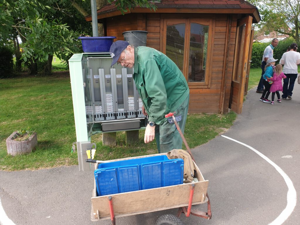 der große Automat am Ententeich wird von Fred Klugmann wieder mit Futterschachteln aufgefüllt