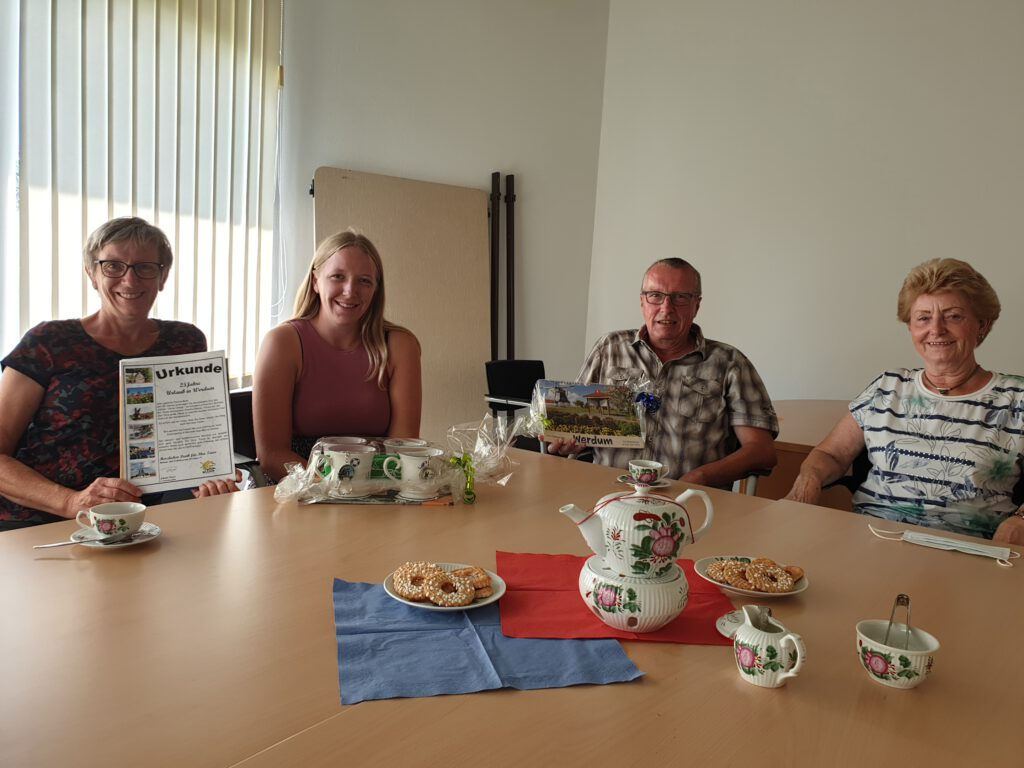 Familie Mast freut sich mit Inge Cremer über Urkunde und Geschenk