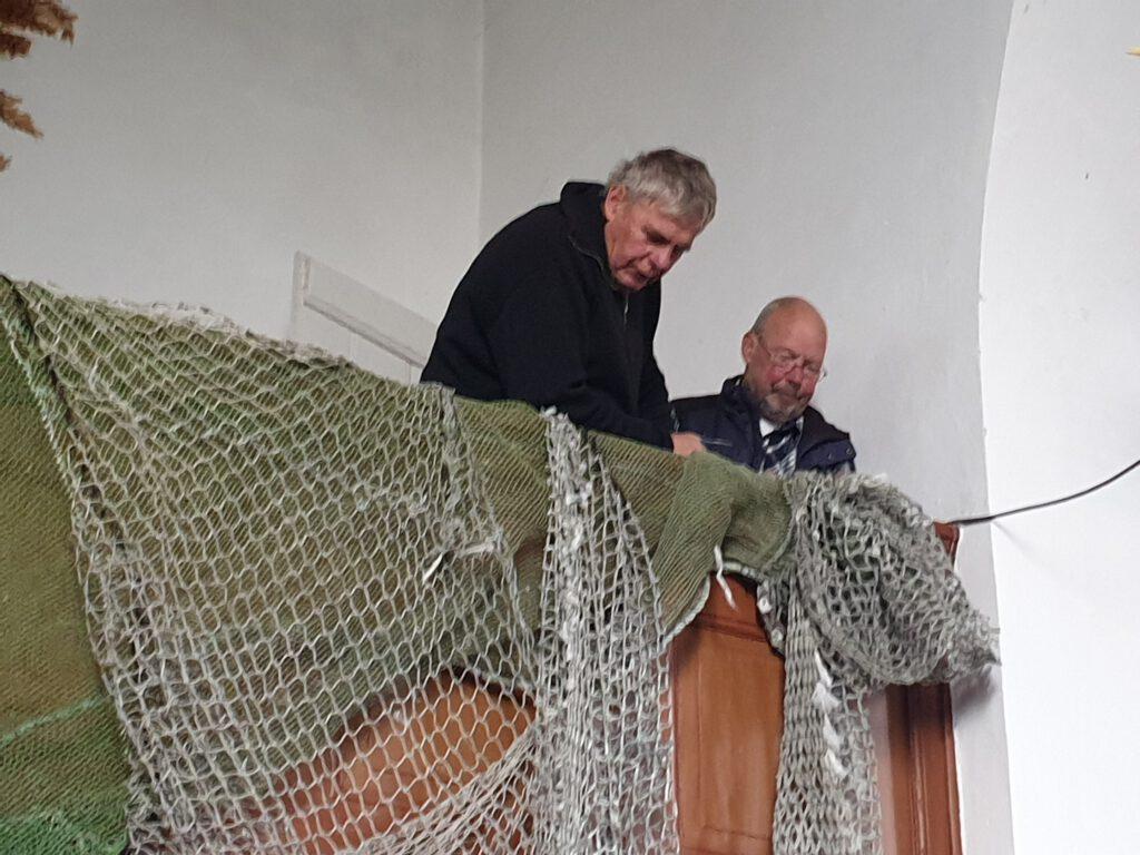 Willi Jacobs und Karl-Heinz Ockenga befestigen ein Fischernetz
