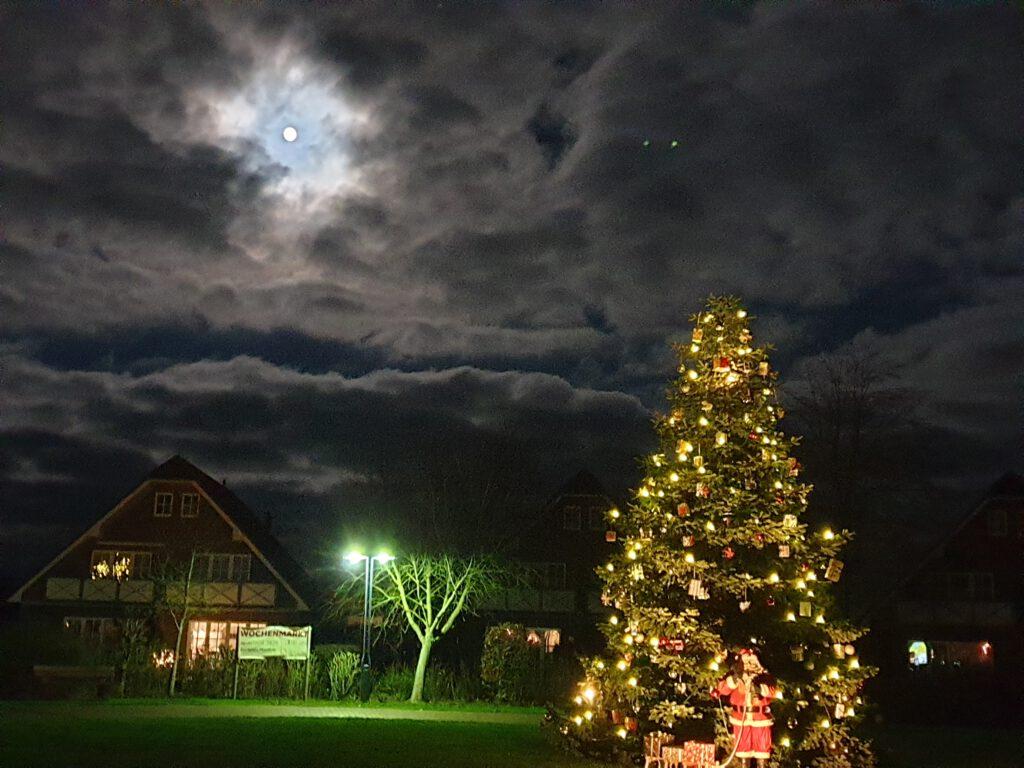 atemberaubender Himmel mit Mond und Weihnachtsbaum auf dem Dorfplatz
