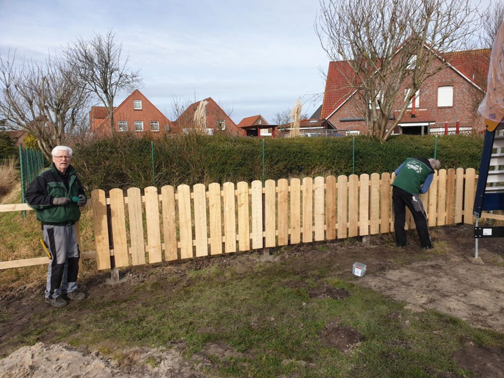 Der Zaun am Kinderspielplatz wird von Heinz Olbertz und Heinz-Theo Emken montiert