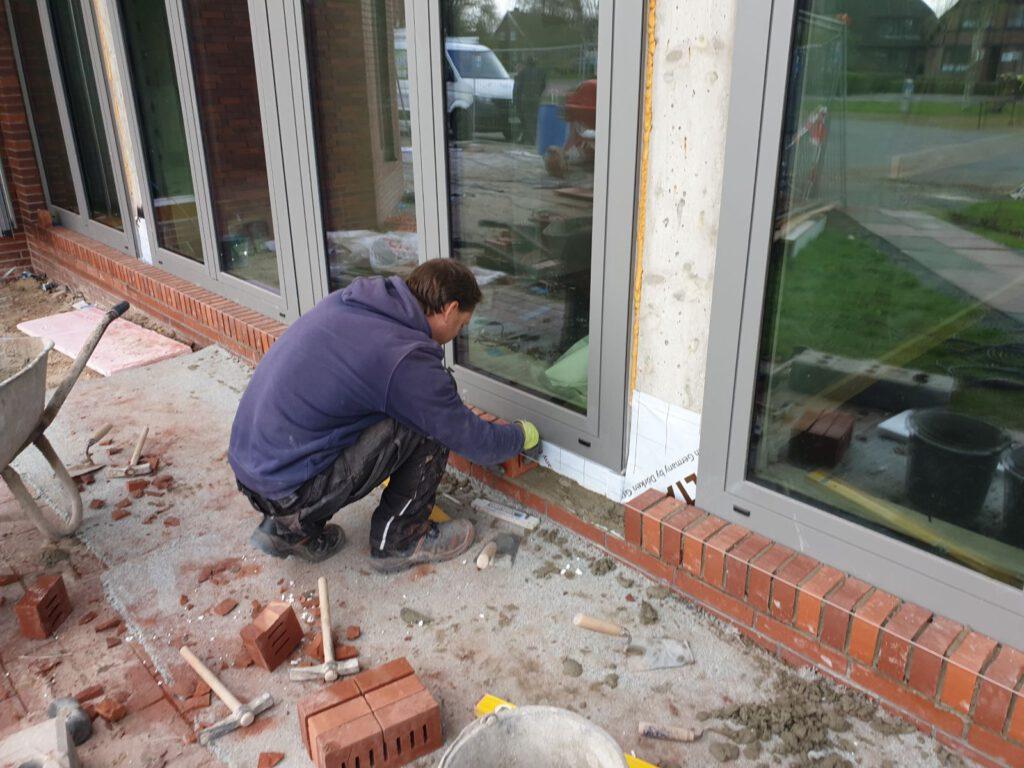 mauert die Sockel unter den neuen Fenstern