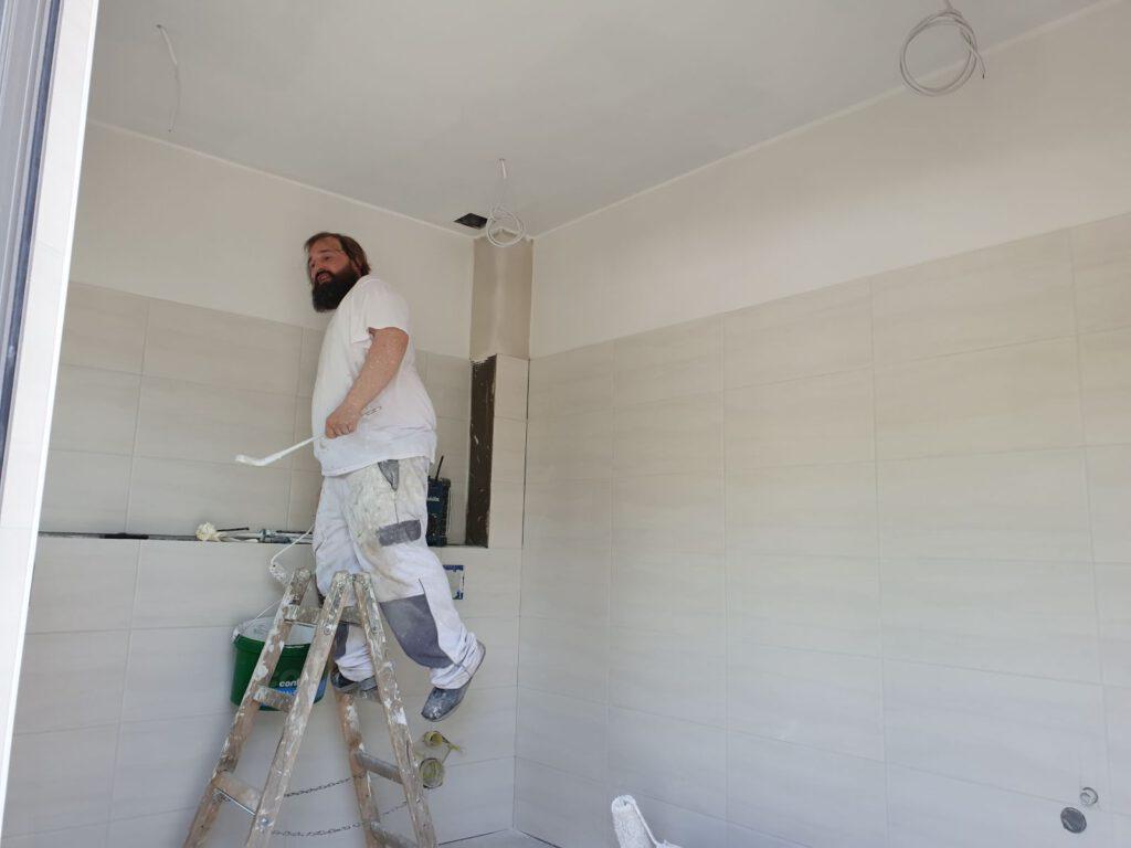 Der Maler mit Pinsel auf der Leiter im Sanitärraum