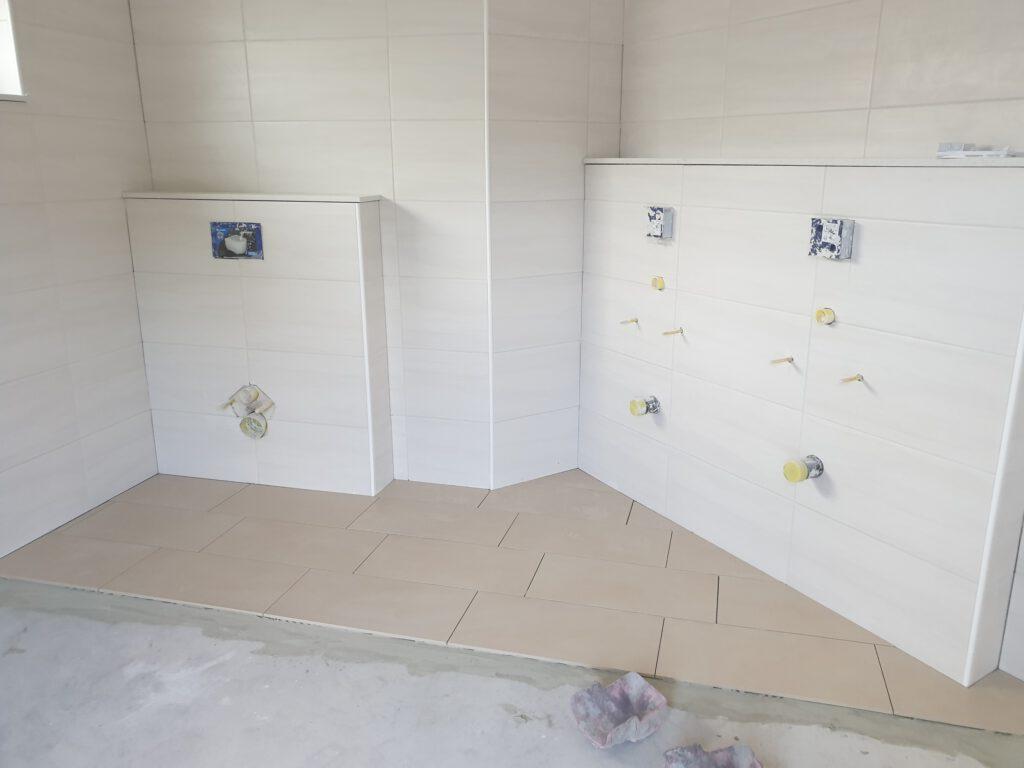 Die ersten Bodenfliesen liegen in der Herren-Toilette