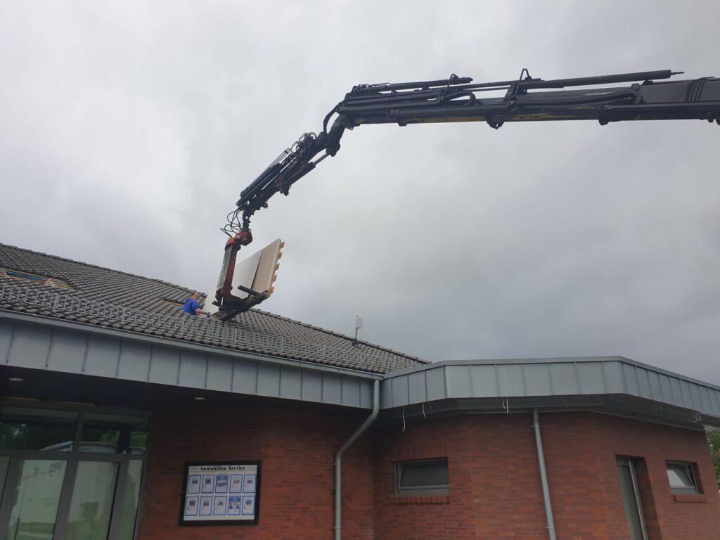 Mit dem Kran werden die Dämmplatten durch das Dach auf den Dachboden gehoben.