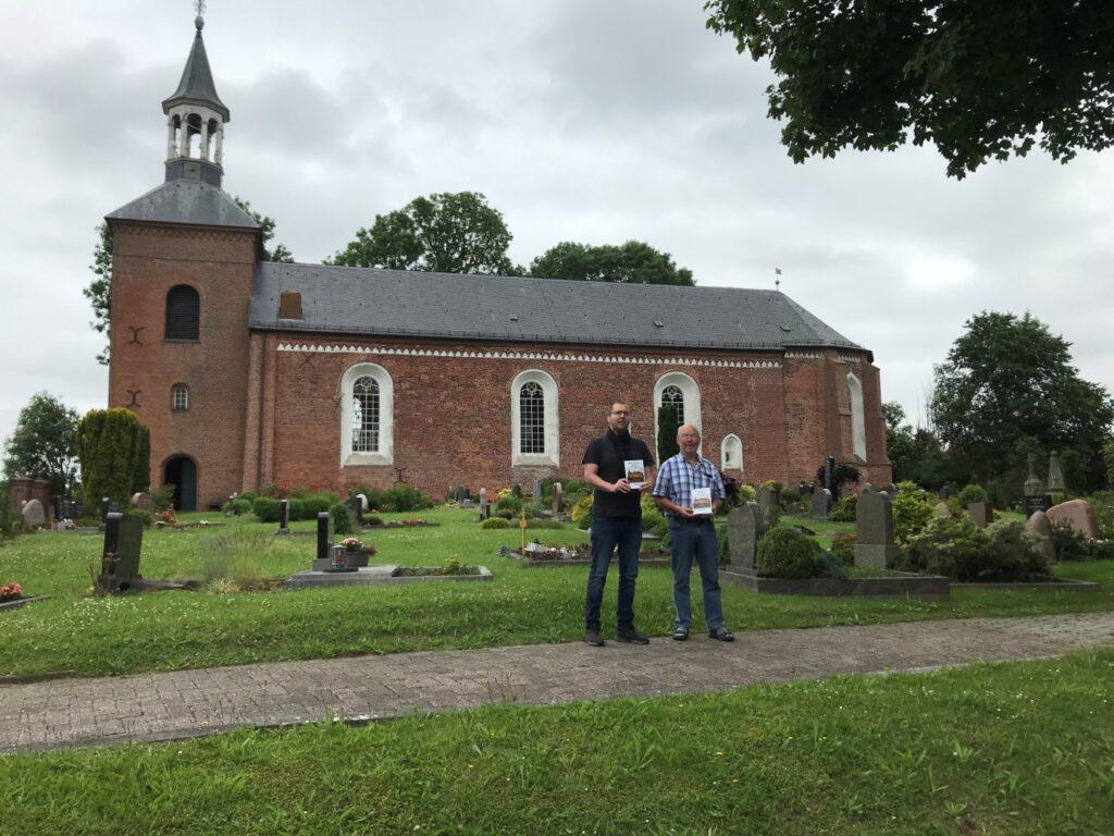 Rainer Hinrichs und Karl-Heinz Ockenga, Vorsitzender des Kirchenvorstands, präsentieren den neuen Kirchenführer