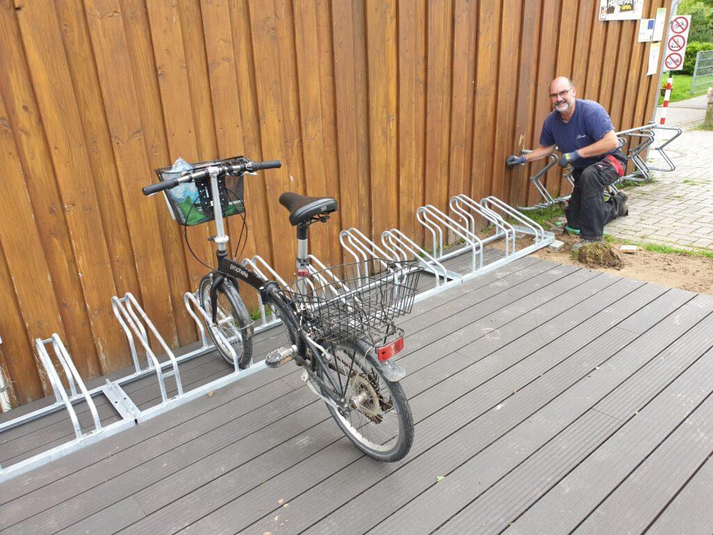 Detlev Reupert schraubt das letzte Element fest, das Dienst-Fahrrad ist schon mal eingeparkt