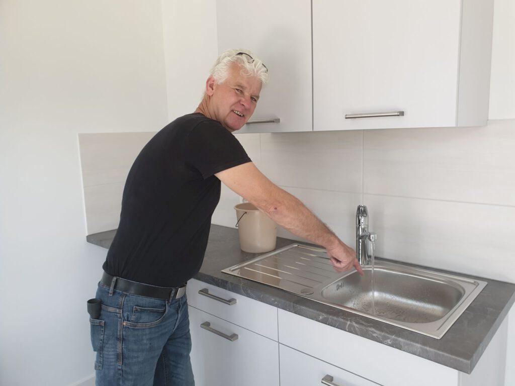 """""""Das Wasser läuft"""". RaiVo-Hausmeister """"Hille"""" Penning hat die neue Küchenzeile für Bankmitarbeiter eingebaut."""