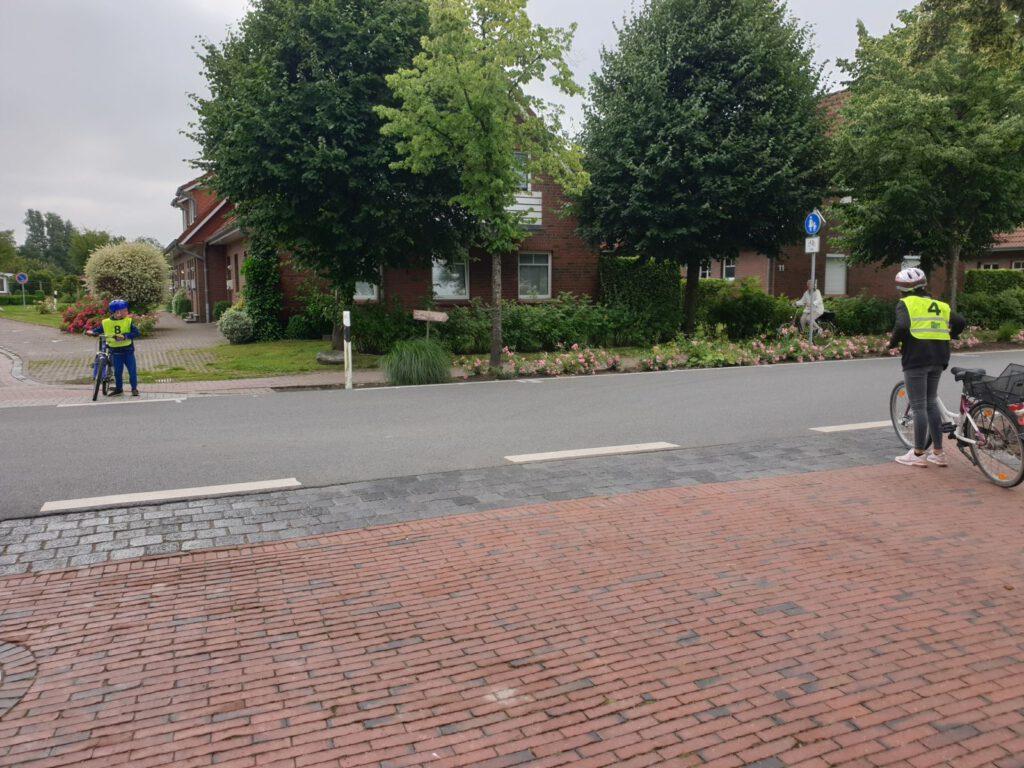 Die Kinder machen es richtig. Absteigen, in beide Richtungen sehen und erst dann die Straße überqueren.
