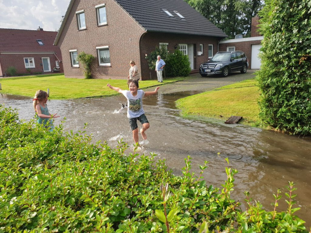 Jubelnd durch das knöcheltiefe Wasser. Majoke und Paul genießen den ungewohnten Spielplatz