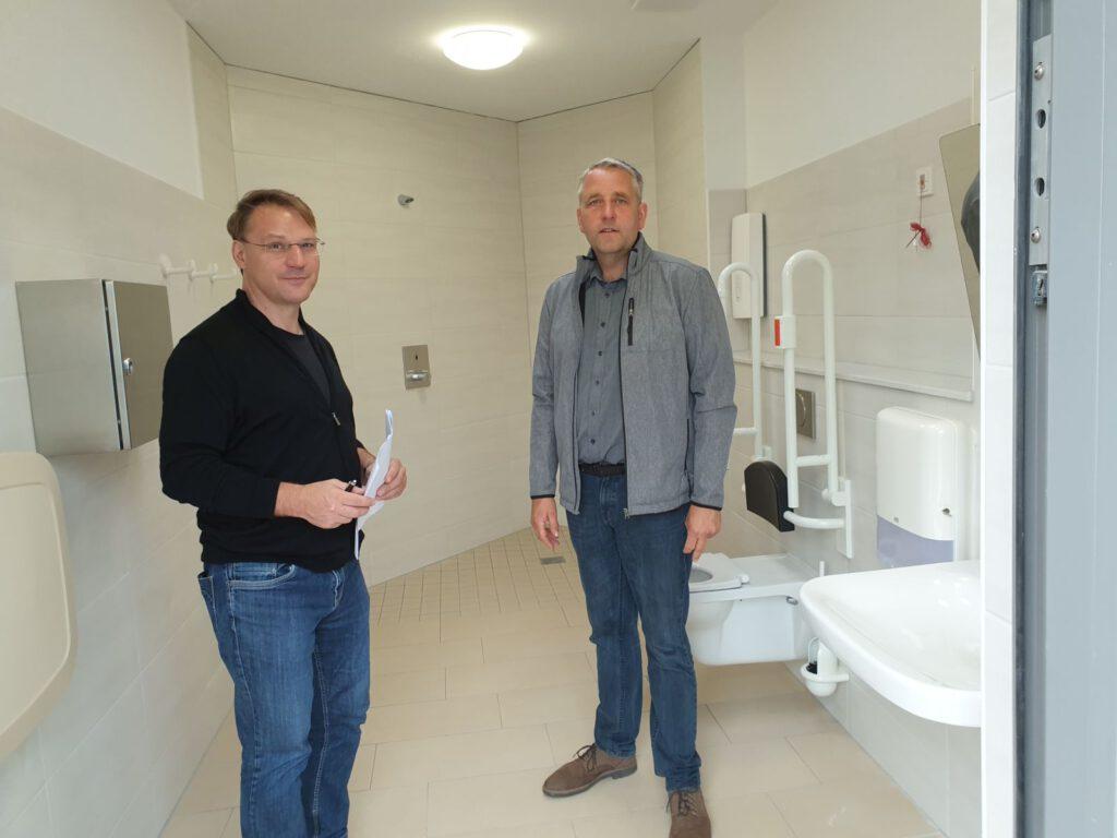 Ingo Eschen und René Weiler-Rodenbäck inspizieren die Behindertentoilette mit Dusche