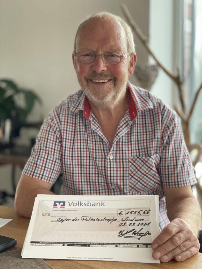 Kalle Ockenga zeigt stolz den Scheck mit den erwirtschafteten 1.555,55 € für die Flutopfer